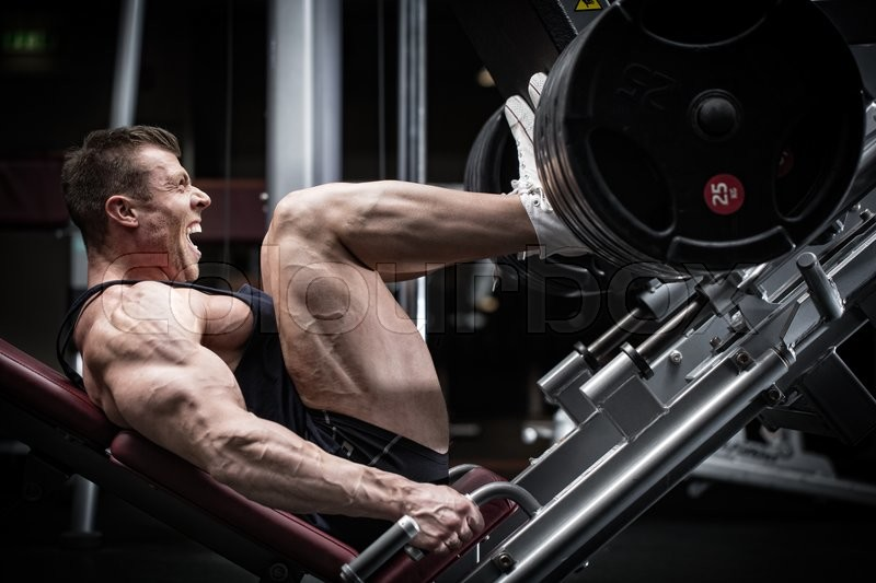 Stock image of 'Man in gym training at leg press to define his upper leg muscles'