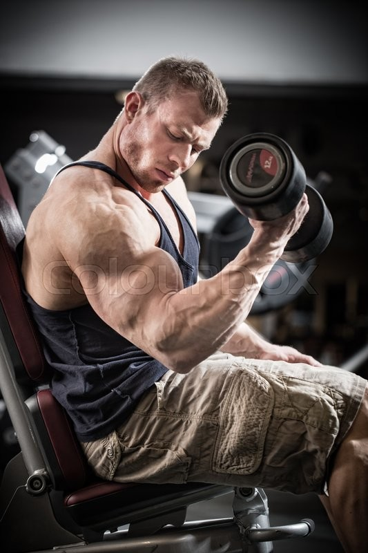 Stock image of 'Man at fitness training with dumbbells in gym sitting on a weight bench'