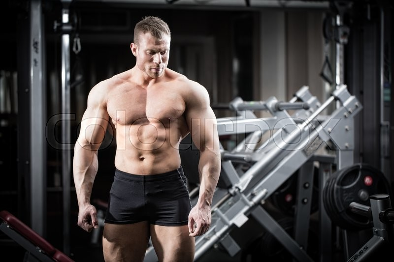 Stock image of 'Strong man doing bodybuilding in gym standing in front of a dumbbell rack'