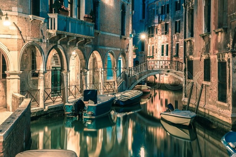 Stock image of 'Lateral canal and pedestrian bridge in Venice at night with street light illuminating bridge and houses, with docked boats, Italy. Toning in cool tones'