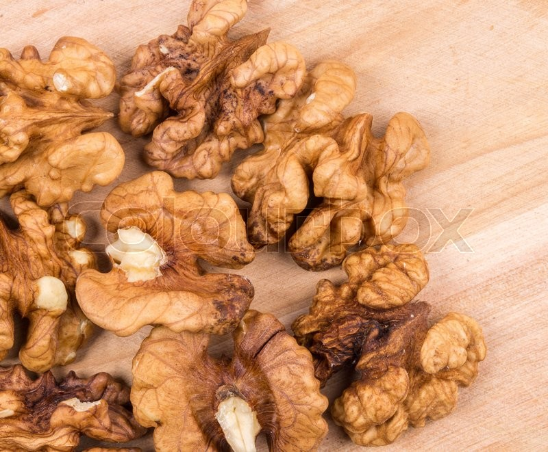 Stock image of 'Close up of walnut kernels on wood table. Whole background.'