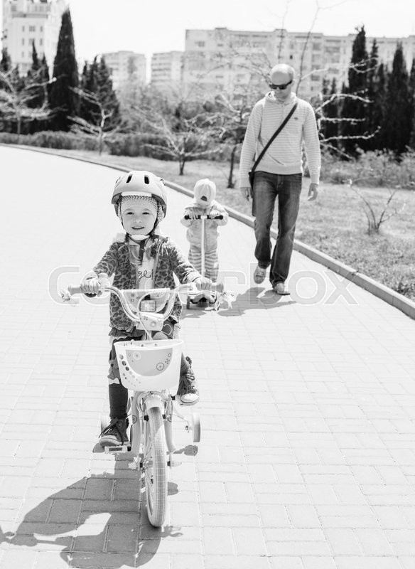 Stock image of 'Happy little girl on a bicycle with his father and brother ( black and white )'