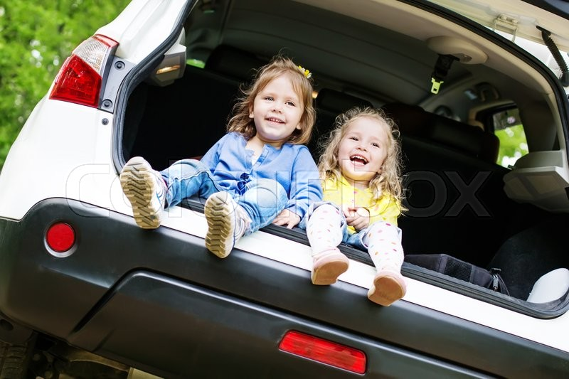 Stock image of 'laughing toddler girls sitting in the car in the forest'