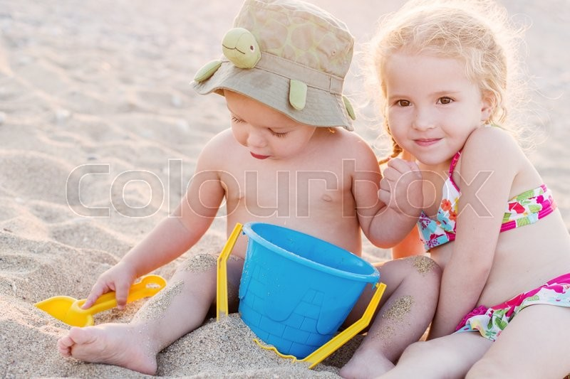 Stock image of 'cute little brother and sister playing on the beach in summer'