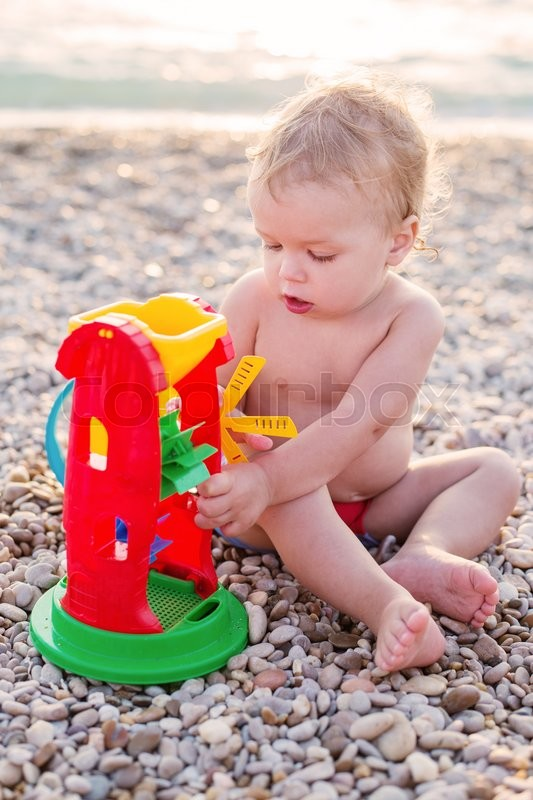 Stock image of 'cute toddler boy playing on the beach in summer'