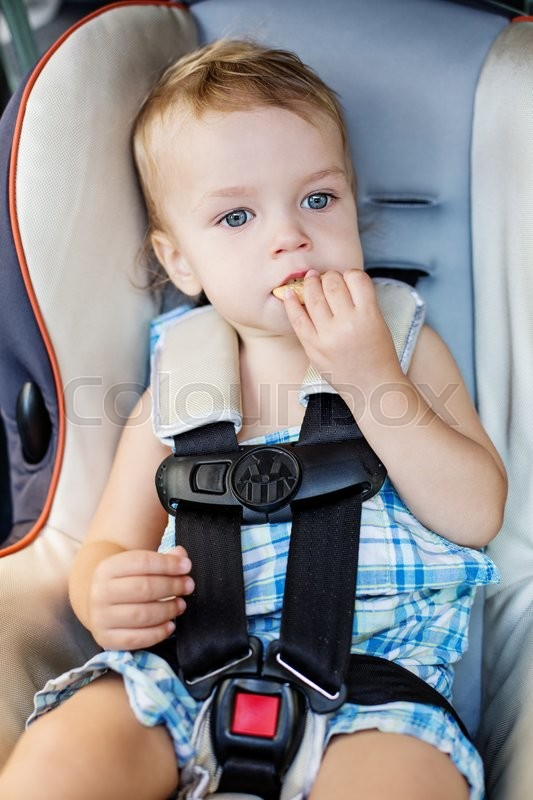 Stock image of 'Happy Toddler boy in the car eating cookies'