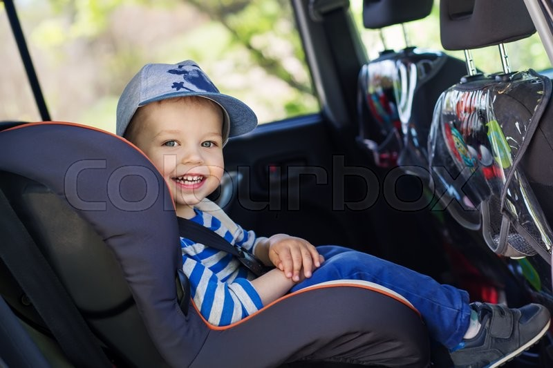 Portrait happy toddler boy sitting in the car seat, stock photo