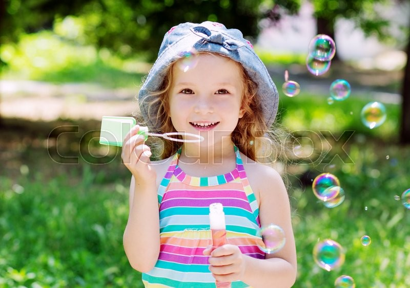 Stock image of 'todddler happy girl blowing soap bubbles in the park'