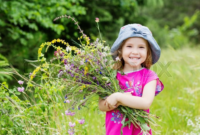 Stock image of 'Happy toddler girl holding a bouquet of wildflowers'