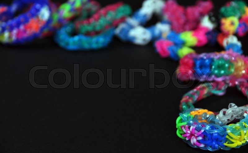 Stock image of 'colorful background rainbow colors rubber bands loom bracelets on black background'