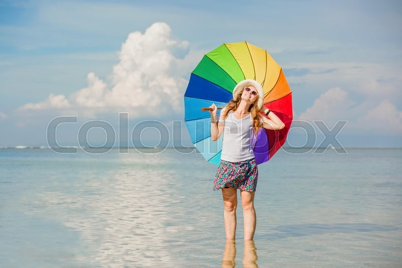 Stock image of 'Cheerful caucasian young woman with rainbow umbrella having fun on the Jimbaran beach on Bali with beautiful ocean and blue sky on background'