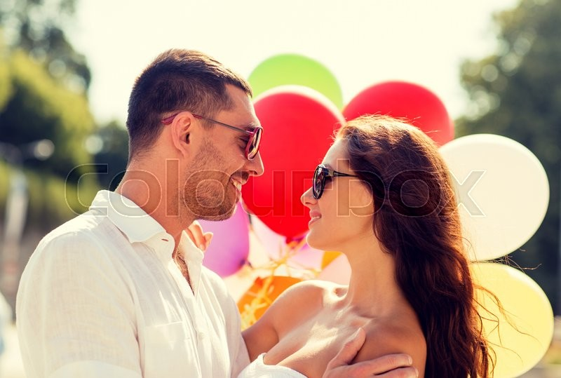 Stock image of 'love, wedding, summer, dating and people concept - smiling couple wearing sunglasses with balloons hugging in park'