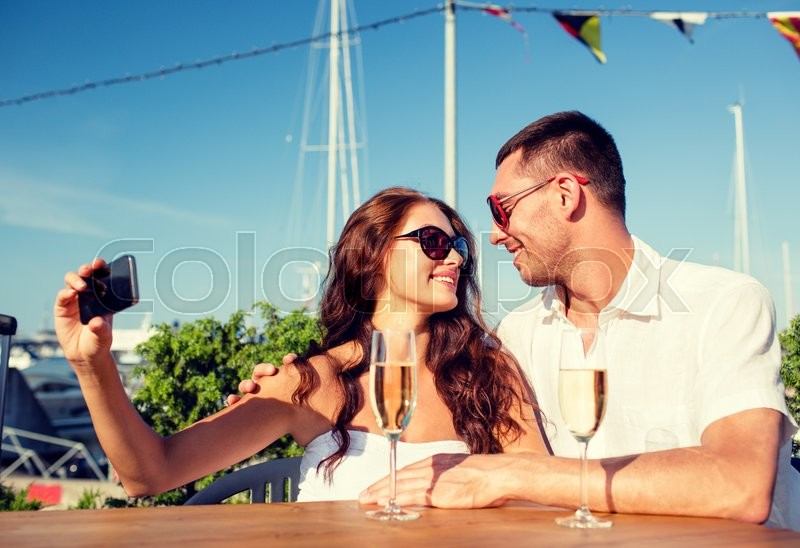 Stock image of 'love, dating, people and holidays concept - smiling couple wearing sunglasses drinking champagne and making selfie at cafe'
