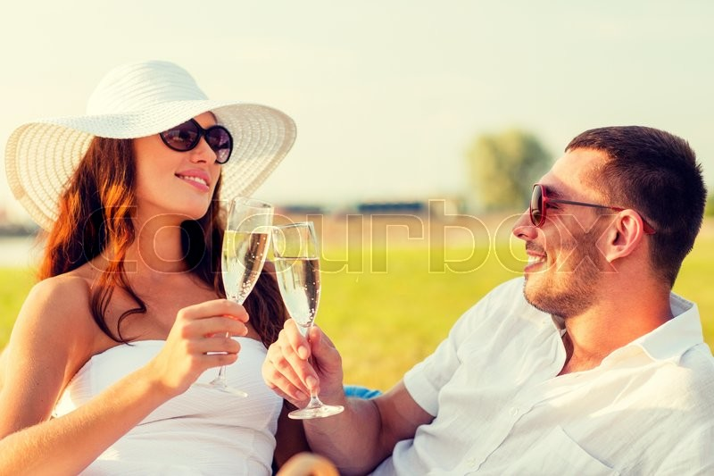 Stock image of 'love, dating, people and holidays concept - smiling couple drinking champagne on picnic'