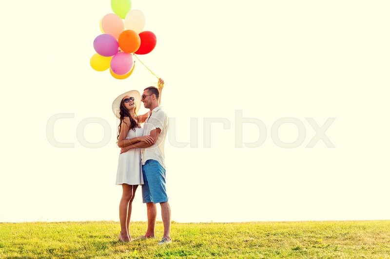 Stock image of 'love, wedding, summer, dating and people concept - smiling couple wearing sunglasses with balloons hugging outdoors'