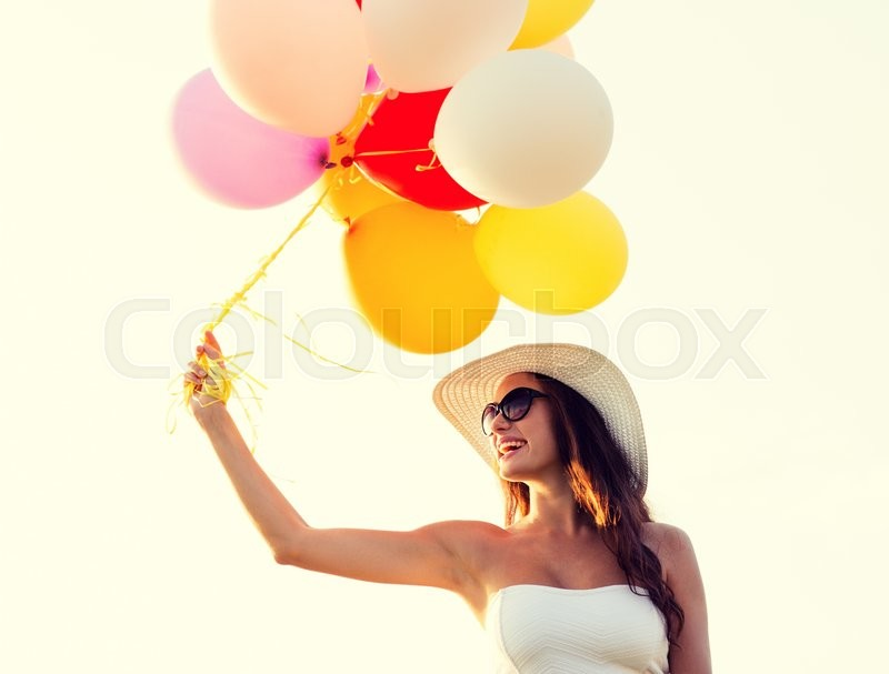 Stock image of 'happiness, summer, holidays and people concept - smiling young woman wearing sunglasses with balloons outdoors'