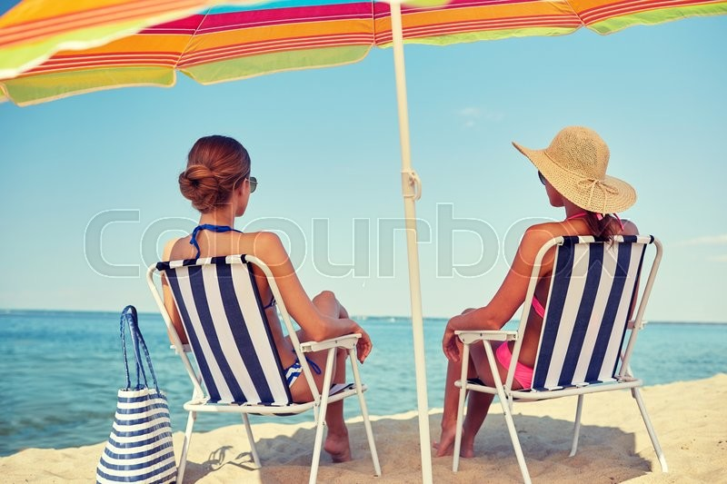 Summer vacation, travel and people concept - happy women sunbathing in lounges on beach, stock photo