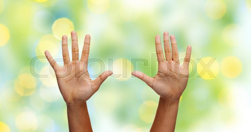 Stock image of 'gesture, people and body parts concept - african woman two hands showing palms or making high five over green lights background'