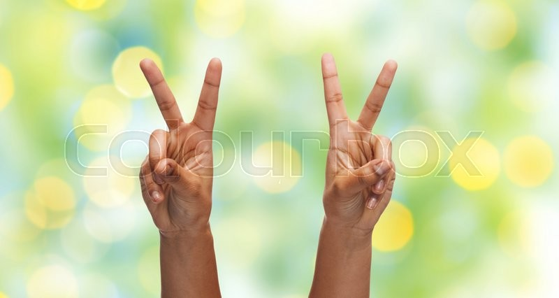 Stock image of 'gesture, people and body parts concept - african woman two hands showing victory or peace over blue sky and clouds background'
