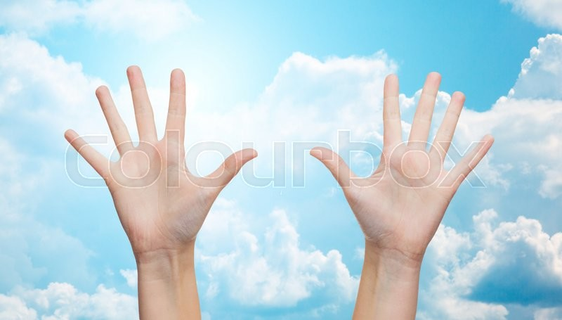 Stock image of 'gesture, people, and body parts concept - two woman hands showing palms or making high five over blue sky and clouds background'