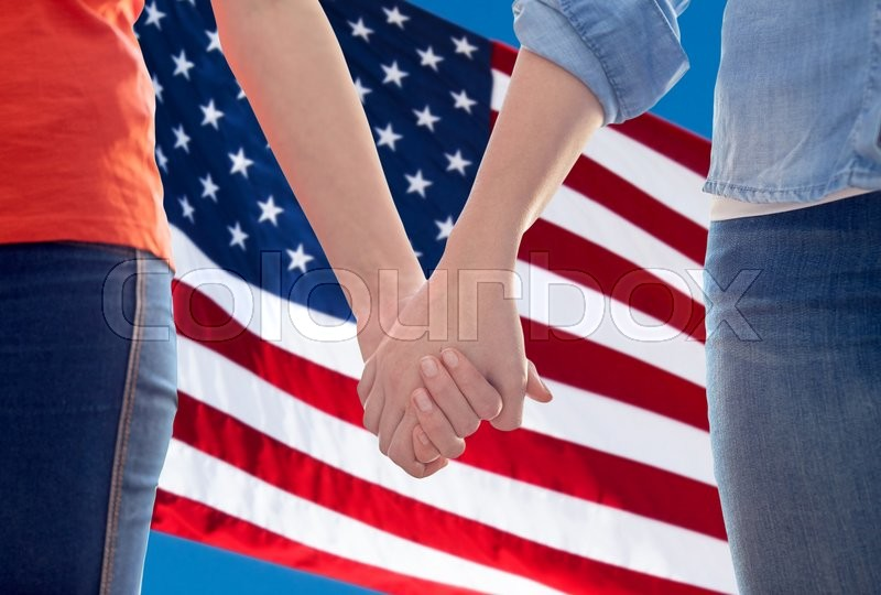 Stock image of 'people, homosexuality, same-sex marriage, gay and love concept - close up of happy lesbian couple holding hands over american flag background'
