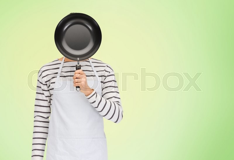 Stock image of 'people, cooking, culinary and identity concept - man or cook in apron hiding his face behind frying pan over green natural background'