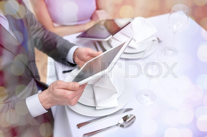 Stock image of 'technology, people, food and holiday concept - close up of couple with menus on tablet pc computers at restaurant over holidays lights background'
