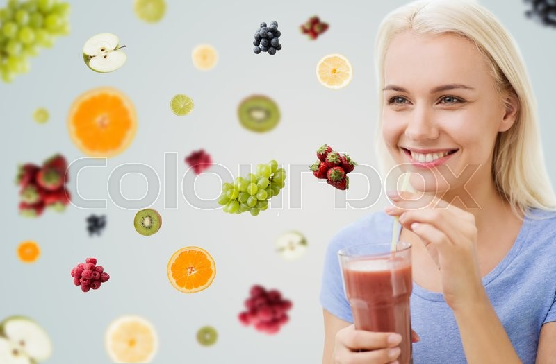 Stock image of 'healthy eating, vegetarian food, dieting and people concept - smiling woman drinking juice or shake from glass over fruits and berries on gray background'