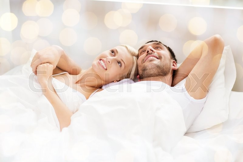 People, family, bedtime and happiness concept - happy couple lying in bed at home over lights background, stock photo