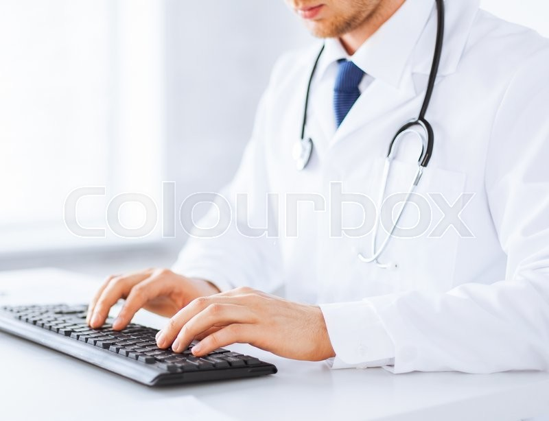 Stock image of 'close up of male doctor typing  on the keyboard'