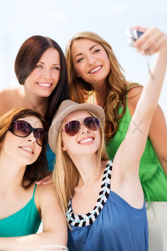 Stock image of 'summer holidays and vacation - girls taking photo in cafe on the beach'