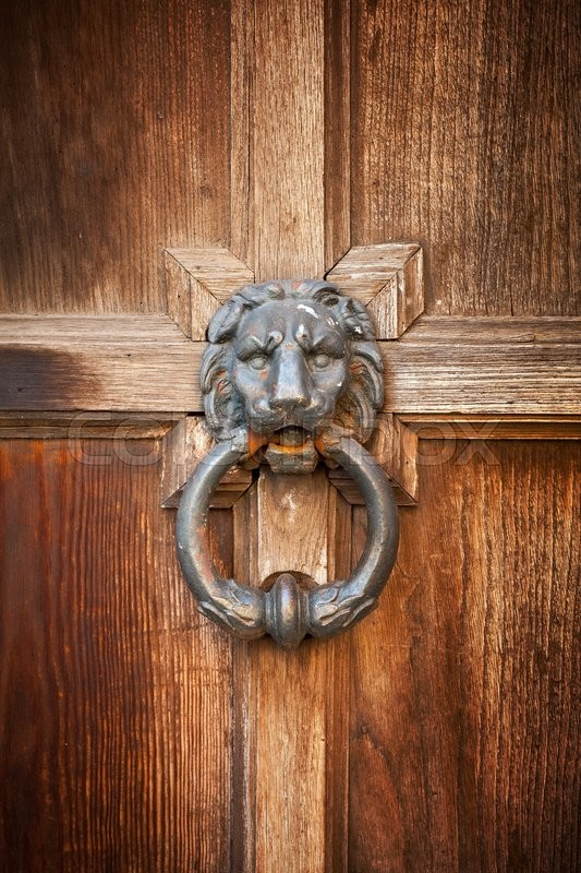 Stock image of 'Old doorknob in shape of lion head with ring on vintage wooden door'