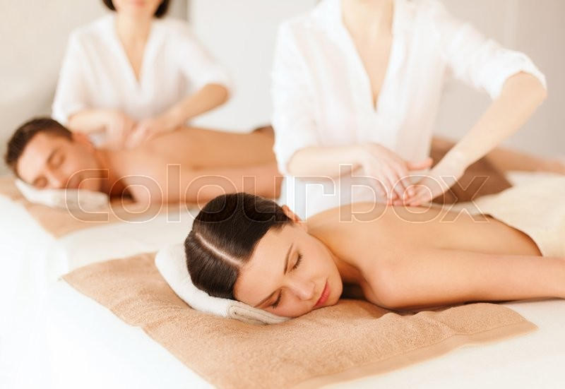 Stock image of 'health and beauty, resort and relaxation concept - couple in spa salon getting massage'