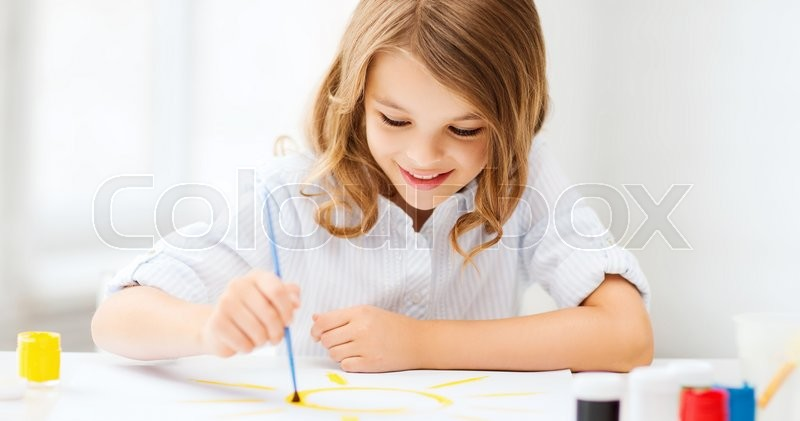 Stock image of 'education, school, art and painitng concept - little student girl painting at school'