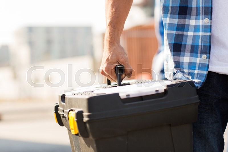 Stock image of 'building, protective gear and people concept - close up of builder carrying toolbox at construction site'