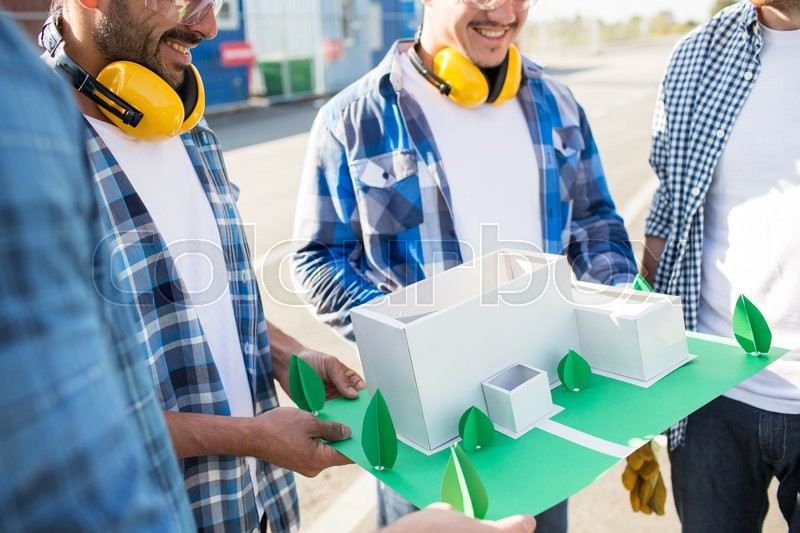 Stock image of 'building, construction, teamwork and people concept - close up of smiling builders with paper house model or layout outdoors'