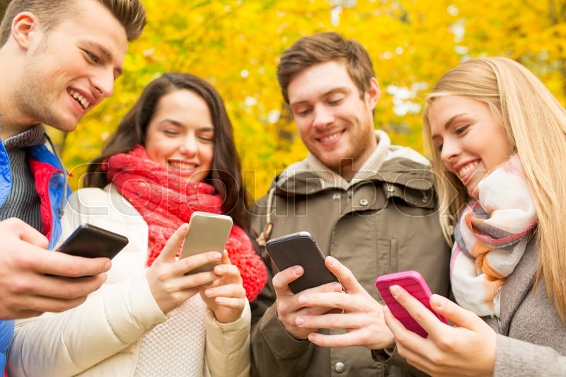 Stock image of 'vacation, people, technology and friendship concept - group of smiling friends with smartphones in autumn park'
