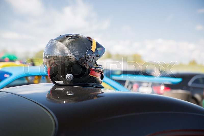 Stock image of 'transportation, high speeds, racing and road concept - close up of car on autodrome or parking with helmet on roof top from back'