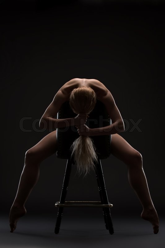 Stock image of 'Art nude picture of naked blonde in the studio. The lighting in the style of low-key.'