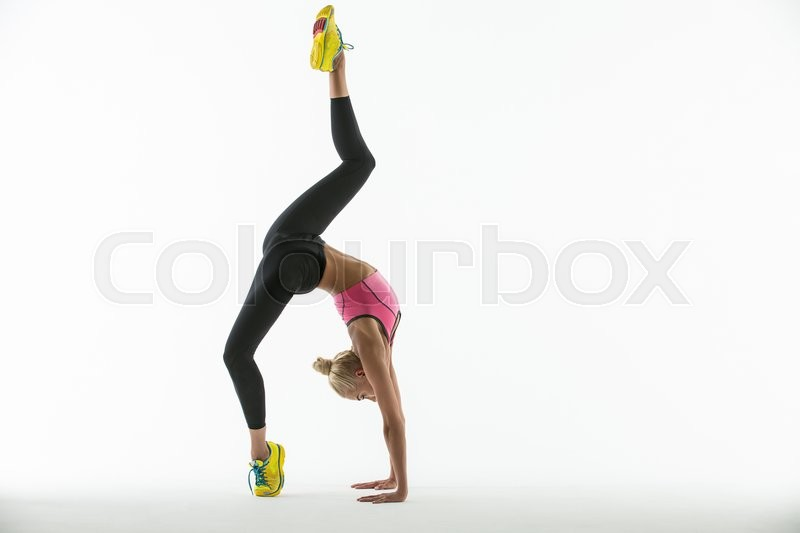 Stock image of 'Rhythmic gymnast in a beautiful sportswear doing exercise in studio.'