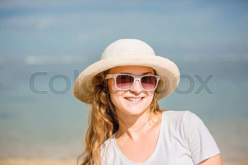 Stock image of 'Bright portrait of attractive young woman in sunglasses on the beach having sunbath. Travel, happiness, vacation concept '