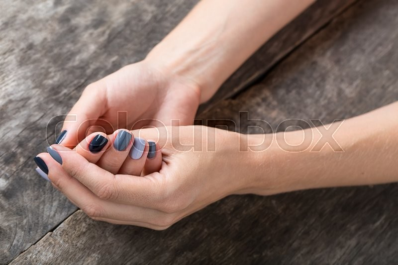 Stock image of 'Beautiful hands with a miniature painted in a gray-colored nail polish. In textural wooden background.'