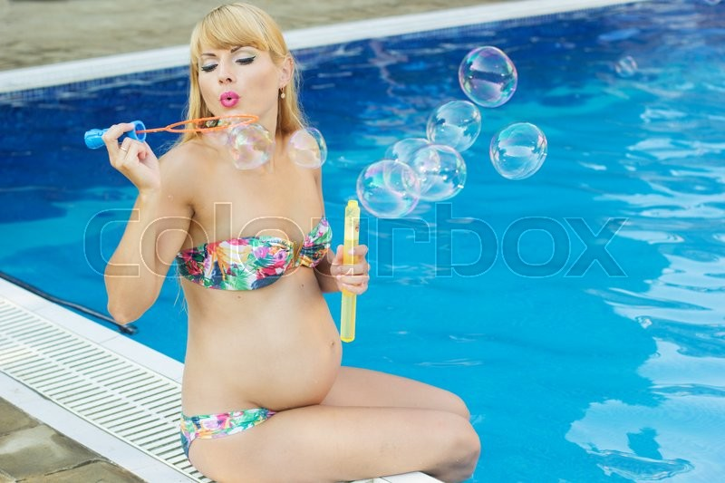 Stock image of 'Beautiful pregnant woman is making soap bubbles near swimming pool with blue water, vacations'