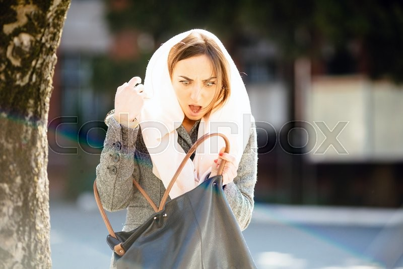 Stock image of 'beautiful girl on the street looking for something in a bag'