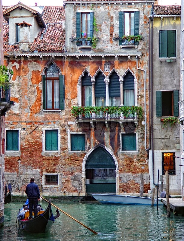 Stock image of 'Scenic canal with gondola and beautiful colored houses'