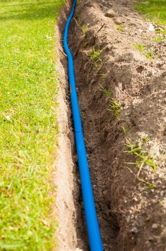 Stock image of 'Cables in a trench protected with blue and yellow plastic tubes.'