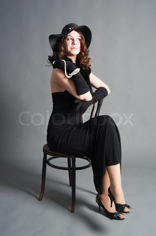 Stock image of 'Beautiful woman in retro style dress sitting on old chair'