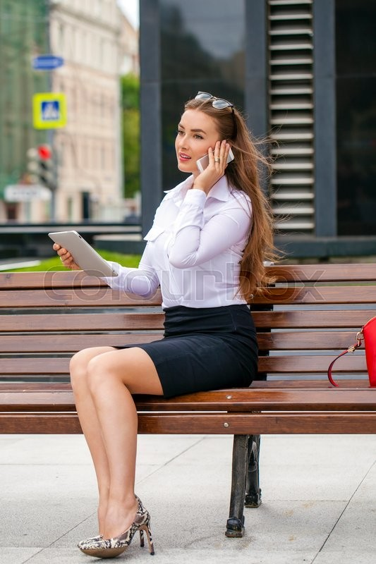 Stock image of 'Young beautiful business woman sitting on a bench in the summer city'