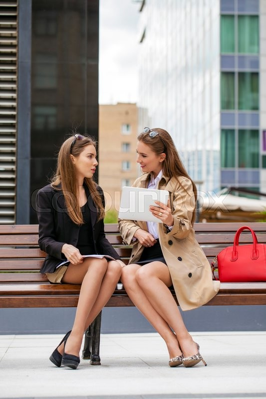 Stock image of 'Two young beautiful business women sitting on a bench in the summer city'