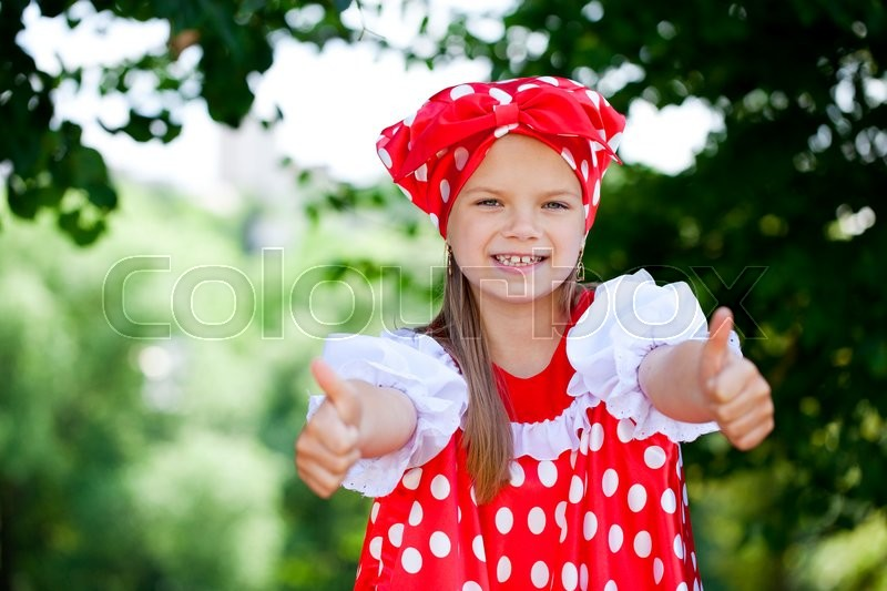 Stock image of 'Portrait of a charming little girl looking at camera, on green summer background'